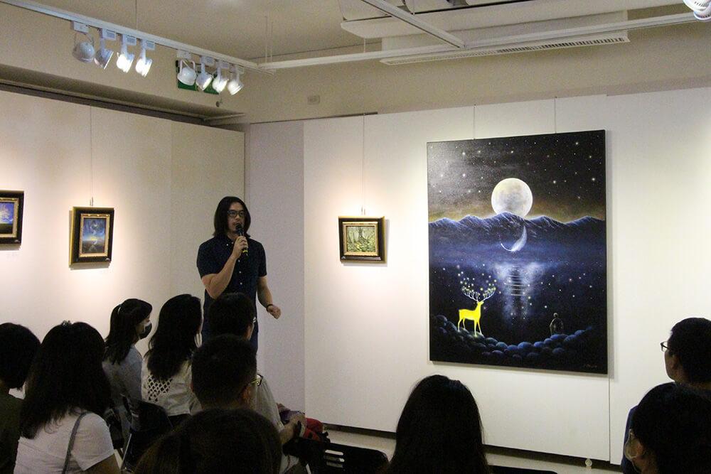 海至於開幕式導覽《與星空的對話》,他的作品就像畫中的羽毛。圖/非池中藝術網攝。