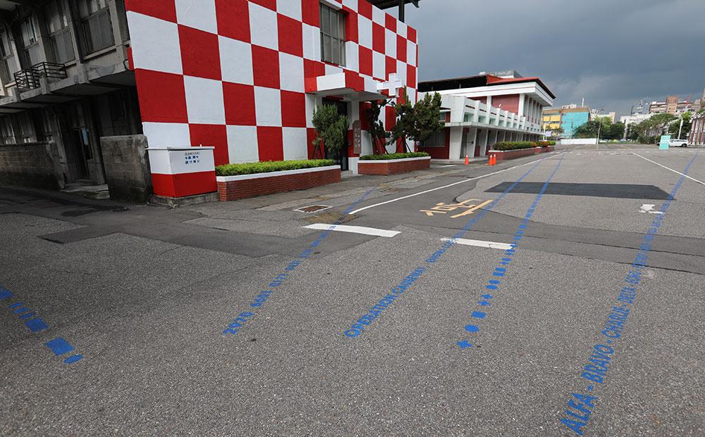 楊俊於園區內漆了六條包含數字、字母、幾何造型等代碼組成的藍線,分別通往實驗場啟動後使用六棟大樓。例如通往原士官大樓的線由摩斯密碼組成。通往軍樂大樓的線則是「歡迎來到台灣當代文化實驗場,台北前空軍總司令部」轉譯成的一組台灣電話號碼。沿著「Alpha」、「Beta」、「 Charlie」等現在軍用音標走則會到達中山堂。 圖/非池中藝術網攝。