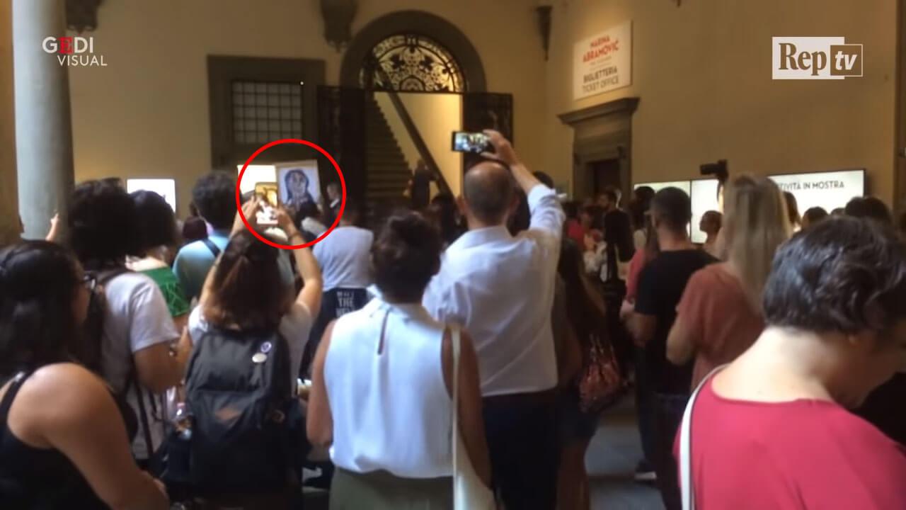 從紅圈處可以看到男子高舉畫布打算攻擊阿布拉莫維奇。圖/翻攝自紀錄阿布拉莫維奇被襲擊經過的影片。